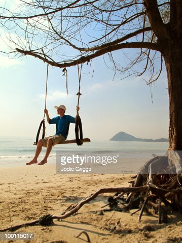 Teenager Sitting on a Large Tree Swing : Foto de stock