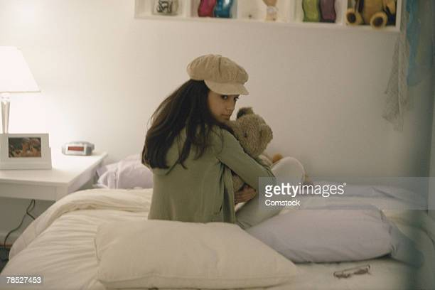 Teenager sitting on bed holding teddy bear