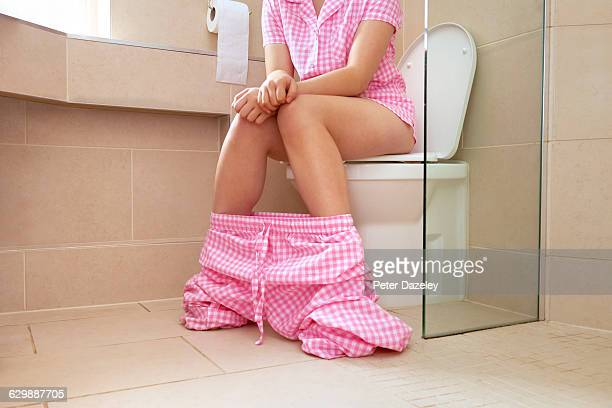 Teenager sitting on the toilet