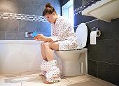 Teenager social networking in bathroom
