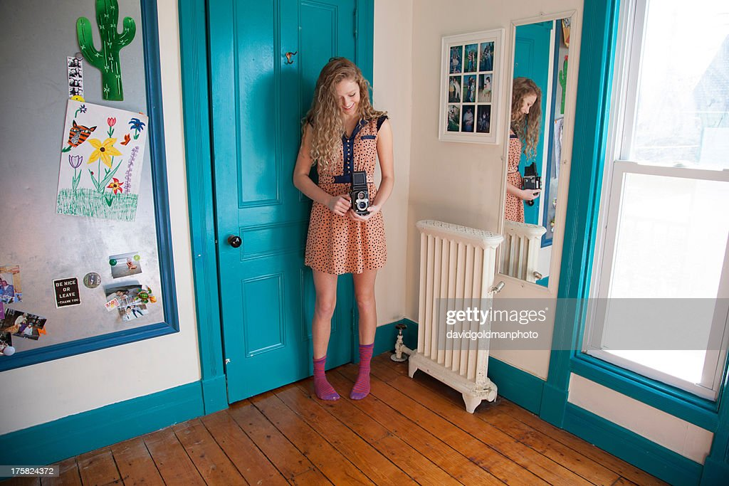 Teenager standing in bedroom with antique camera : Stock Photo