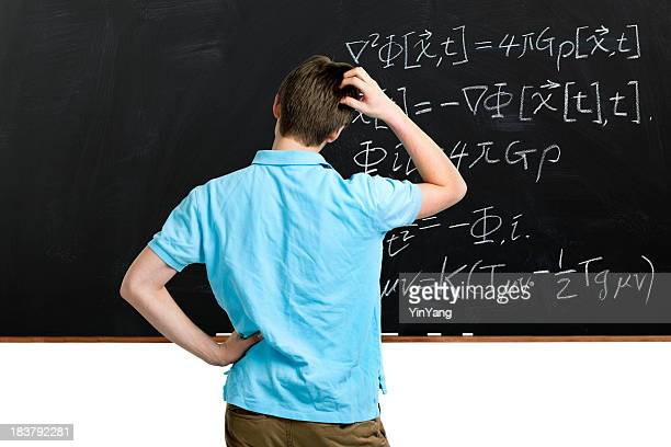 Teenager Student Scratching Head, Pondering Mathematics Formulas on Classroom Blackboard