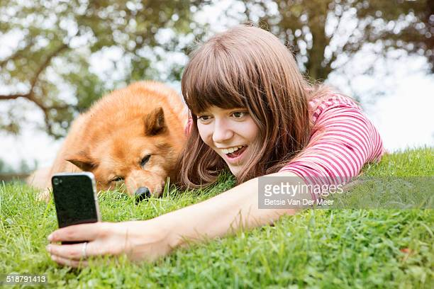 teenager takes Selfie of dog and herself on phone.