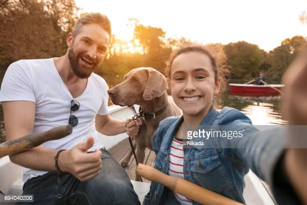 Teenager nehmen Selfie mit Vater und Hund im Ruderboot am See
