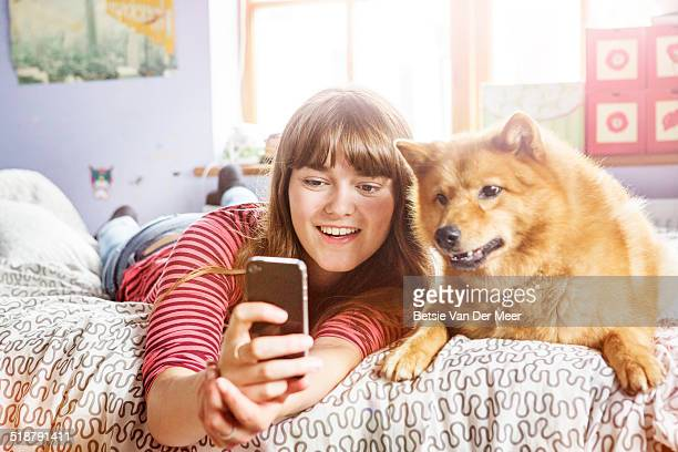 Teenager taking Selfie with her dog on bed..
