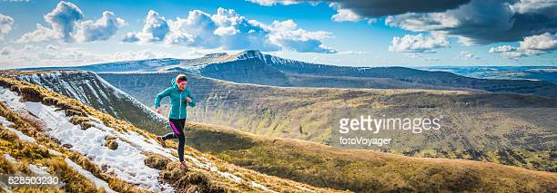 Teenager trail running along mountain path Brecon Beacons panorama Wales
