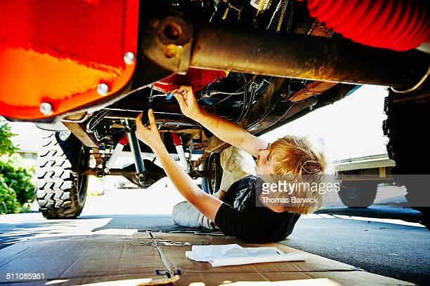 Teenager under vehicle replacing oil pan gasket