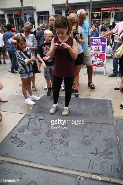 A teenager uses a smartphone to photograph the hand and footprints of cast members of the 'Twilight' films on Hollywood Boulevard Los Angeles...