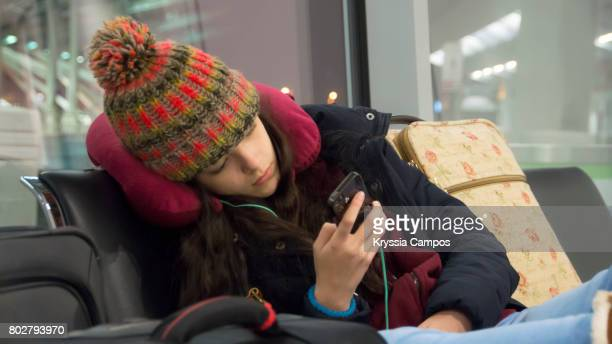 Teenager using cell phone at the airport lounge