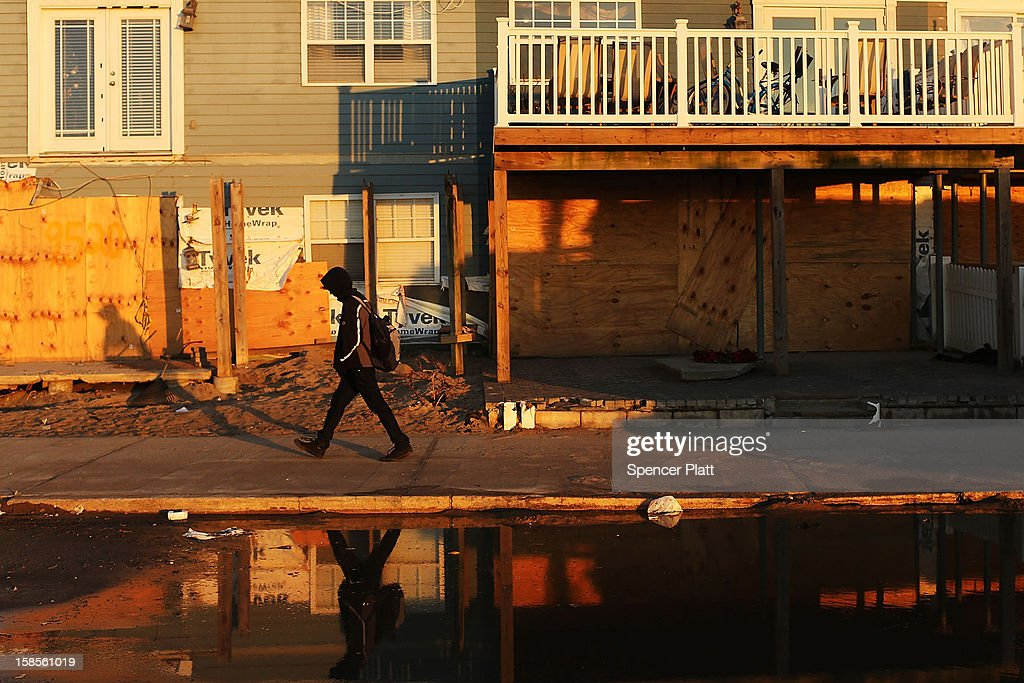 A teenager walks by flood damaged homes in the Rockaway neighborhood, where a large section of the iconic boardwalk was washed away on November 19, 2012 in the Queens borough of New York City. As the holidays approach after Superstorm Sandy slammed into parts of New York and New Jersey, thousands of residents and businesses are still recovering from the devastation.