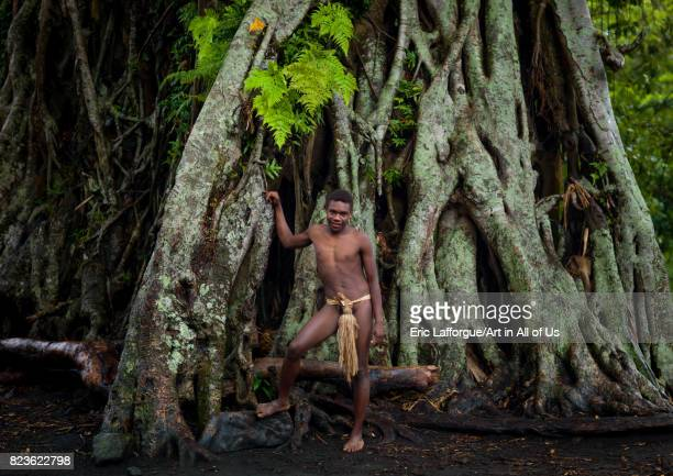 Teenager wearing a penis sheath called a namba standing in front of a giant banyan tree Tanna island Yakel Vanuatu on September 6 2007 in Yakel...