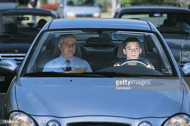Teenager with driving instructor in car