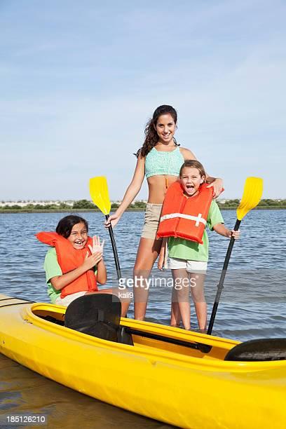 Teenager with girls beside kayak
