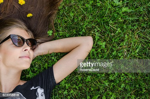 teenager with stylish sunglasses lying on green grass : Stock Photo