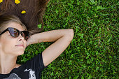 teenager with stylish sunglasses lying on green grass