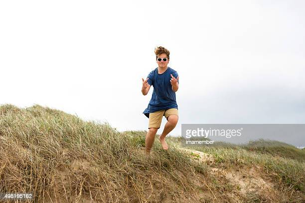 Teenager with sunglasses jumping and showing middle fingers, copy space
