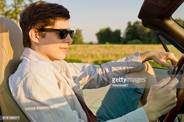 Teenager with sunglasses looking at his smartphone in a convertible car