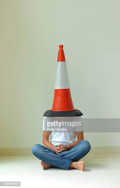 Teenager with traffic cone on his head