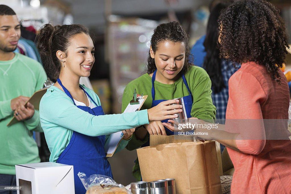 Teenagers accepting donations at food bank warehouse