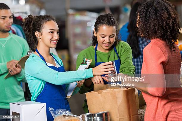 Teenagers accepting donations at food bank warehouse