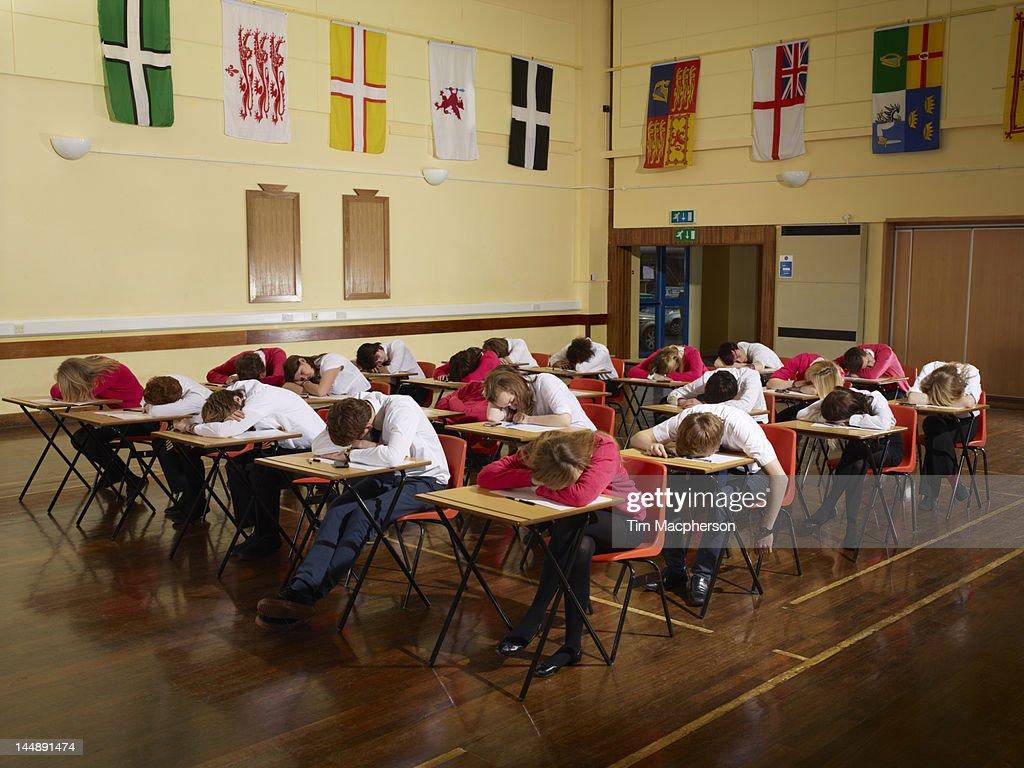 Teenagers asleep in school Hall : Stock Photo