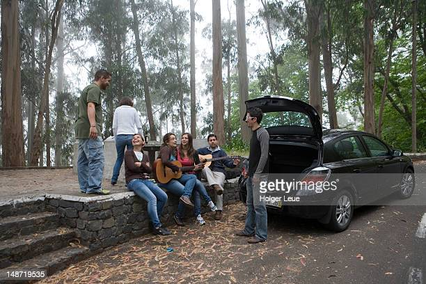 Teenagers at rest stop on roadside.