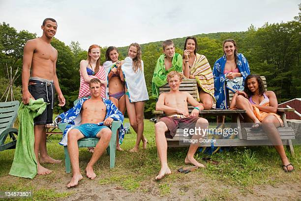 Adolescents se détendre ensemble dans des vêtements dans la campagne piscine