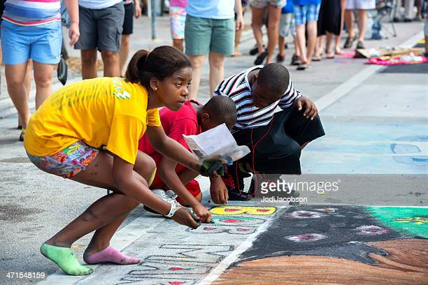 Teenagers creating street art with chalk at festival