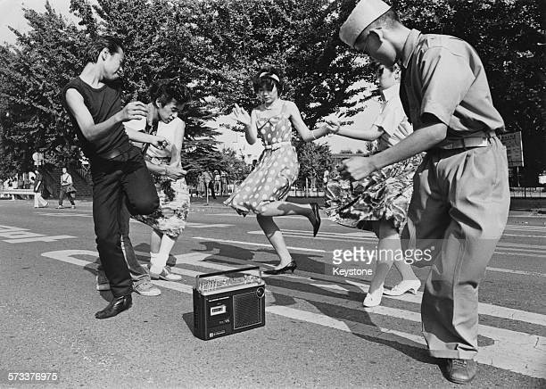 Teenagers dance the twist around a radio cassette recorder in a street in the Harajuku district of Shibuya Tokyo Japan 1978