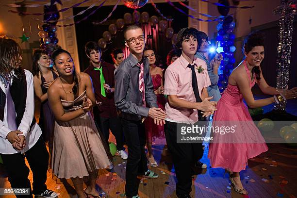 Teenagers dancing together at prom