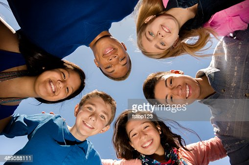 Teenagers: Diverse group of friends huddle outside together. Blue sky.