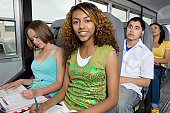 Teenagers Doing Homework While Riding School Bus