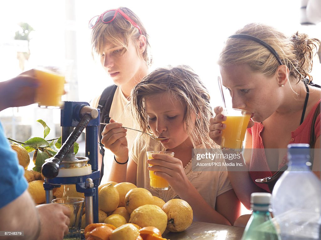 Teenagers drink freshly squeezed juice at stand : Stock Photo