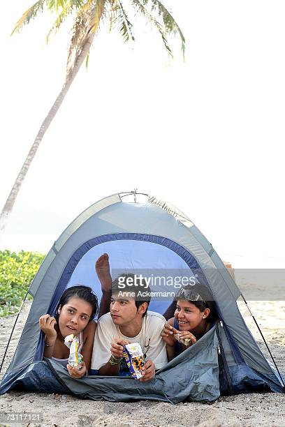 Teenagers (15-17) eating candybars in tent on beach