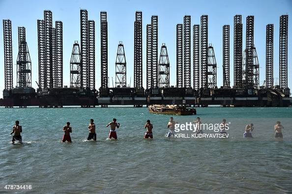 Teenagers from boxing school take part in a training session in the Caspian sea in front of the Soviet oil platform in Baku on June 27 2015 AFP PHOTO...