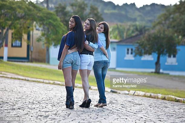 Teenagers girls embraced and walking in  village