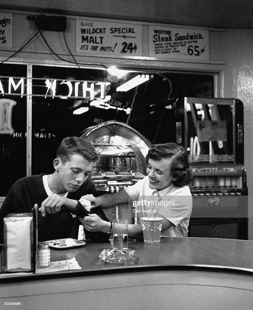 Teenagers going steady, at late-night snack hangout.