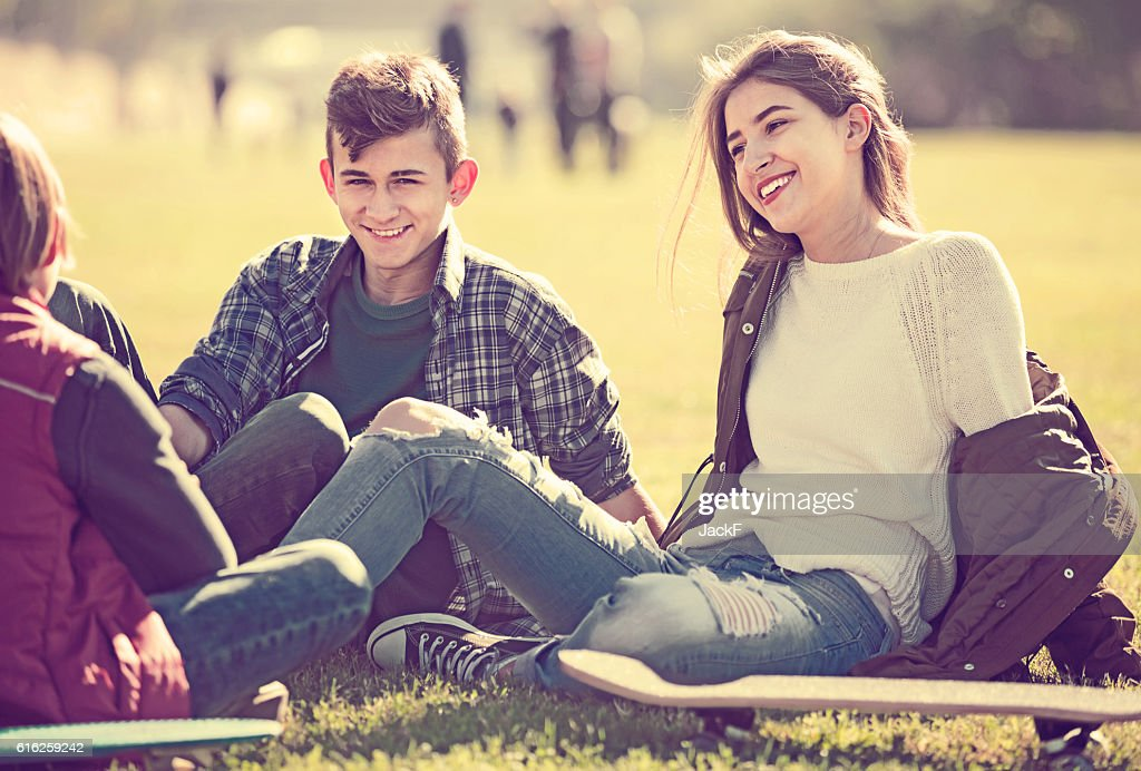 teenagers hanging out outdoors and discussing something : Stock Photo