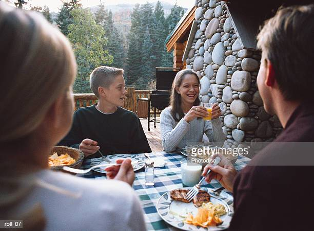 teenagers have breakfast outside at a lodge