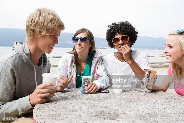 Teenagers having drinks and snacks
