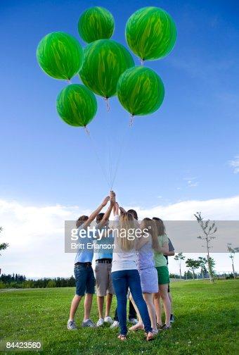 Teenagers holding helium green balloons : Stock Photo