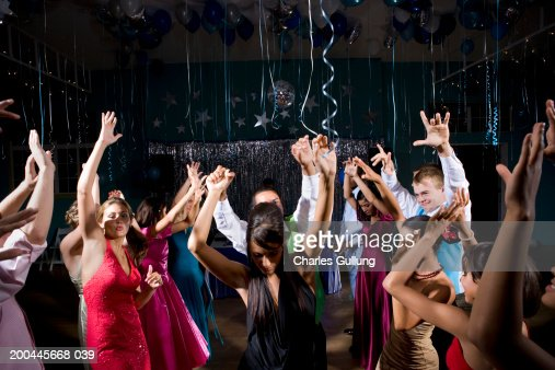 Teenagers (15-18) in formalwear dancing at prom, arms raised
