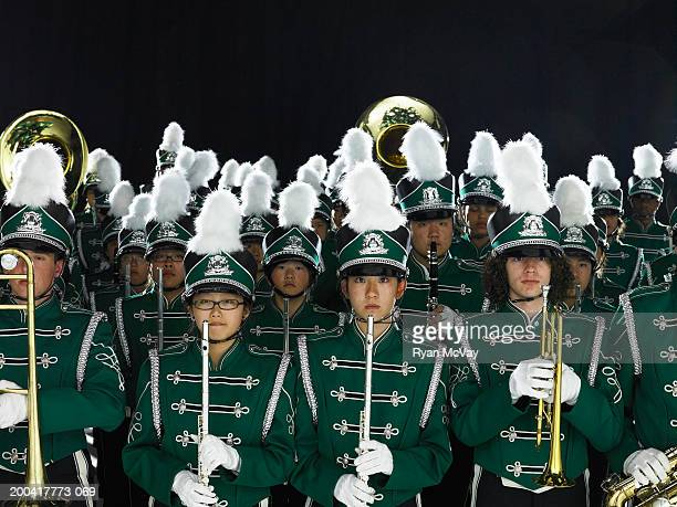 Teenagers (14-18) in marching band uniforms holding wind instruments