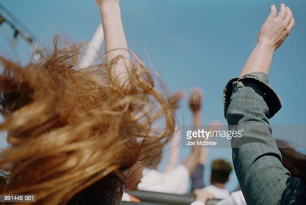 Teenagers in rollercoaster with hands up in air,girl's hair in fore