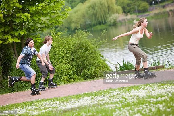 Teenagers inline skating, smiling