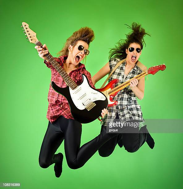 Teenagers jumping and playing the guitar