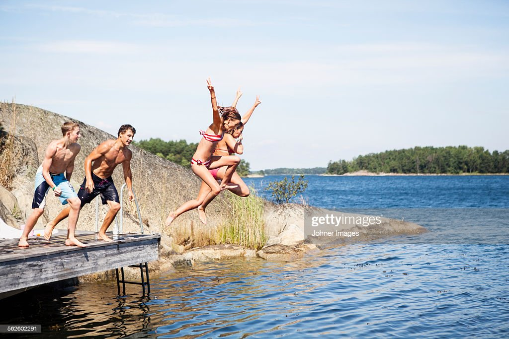 Teenagers jumping into water