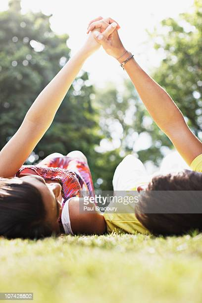 Teenagers laying in grass holding hands