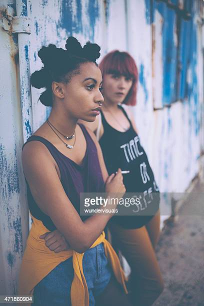 Teenagers leaning against a wall and smoking