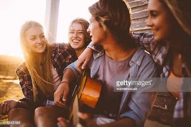 Jugendliche hören Kerl seine Gitarre spielen